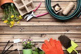 Different garden tools with flowers on wooden table - 243345601