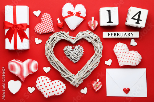 Grey heart with gift box, envelope and wooden cube calendar on red background