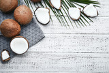 Ripe coconuts with napkin and palm leafs on wooden table
