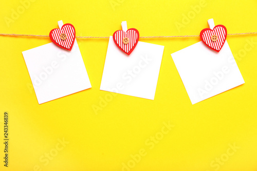 Blank papers hanging on rope with hearts