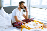 Young man having breakfast in bed and using a mobile phone - 243347815