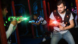 Emotional guy playing laser tag in colorful beams - 243356856