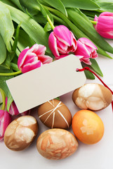 Easter background with bouquet of pink tulips and colorful eggs . © Swetlana Wall