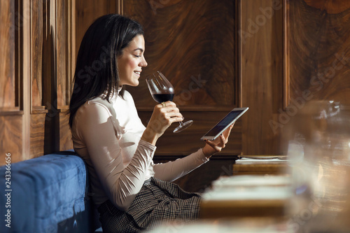 Attractive young business woman drinking red wine while using her digital tablet in a restaurant.