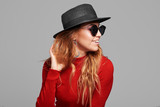 Fashion portrait pretty woman in black rock style hat and sunglasses over grey background. Holiday concept - 243372244
