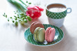 Spring coffee background. Pink tulip, freesia, espresso and macarons with spring flowers