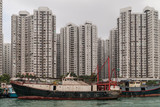 Hong Kong, China  - May 12, 2010: Black and red fishing vessel docked in  harbor with many tall apartment buildings on shore. Foggy silver sky. - 243378205