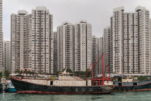 obraz PCV Hong Kong, China - May 12, 2010: Black and red fishing vessel docked in harbor with many tall apartment buildings on shore. Foggy silver sky.