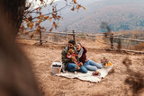 Cute couple on the picnic playing with dog. On blanket flowers, baskets and cookies. Autumn time, in background mountains and forest. - 243379241