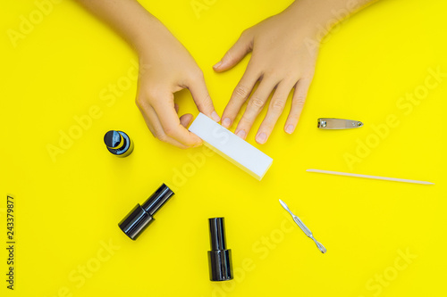 Leinwanddruck Bild Woman Hands Care. Top View Of Beautiful Smooth Woman's Hands With Professional Nail Care Tools For Manicure On yellow Background. Closeup Of Healthy Female Nails With yellow Nail Polish. High