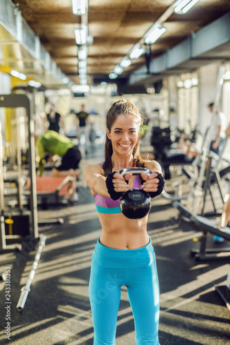 Smiling Caucasian fit woman with ponytail and dressed in sportswear lifting kettlebell while standing in gym.