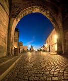 Fototapeta Fototapety pomosty - Romantic Prague at dawn, entrance to Charles Bridge through the illuminated arch of Lesser Town Bridge Tower © tilialucida