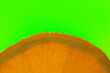 Leinwandbild Motiv orange slice with bubbles on a green background.