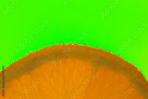 Leinwandbild Motiv orange slice with bubbles on a green background.