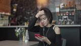 Close-up portrait of young girl with short dark hair in a black top sitting in a cafe and listening to music in earphones. - 243391640