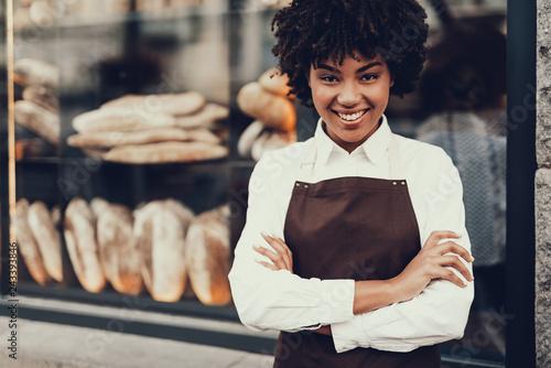 Leinwandbild Motiv Attractive lady standing near bakery shop and smiling