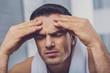Sad cheerless man holding his forehead