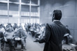 Rear view of speaker giving a talk at business meeting. Audience in the conference hall. Business and Entrepreneurship concept. Black and white blue toned image. - 243396033