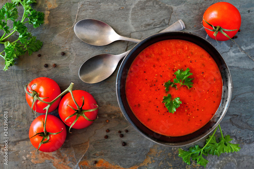Leinwandbild Motiv Homemade tomato soup. Above view, table scene on a dark slate background.