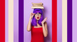 Portrait of young style hipster girl with purple hair and books on purple color background