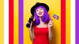 Portrait of young style hipster girl with purple hairstyle with binoculars and Great Britain flag in hand on yellow background - 243397210