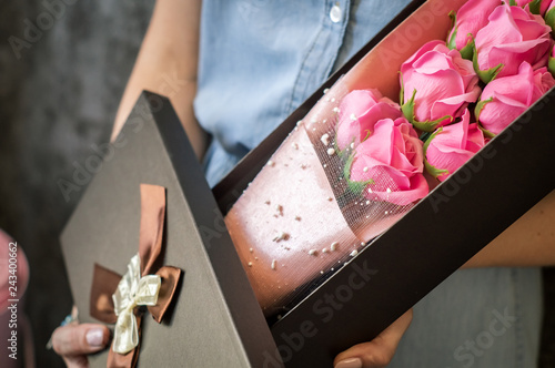 Florist's work: A girl demonstrates a box with a bouquet of pink roses.
