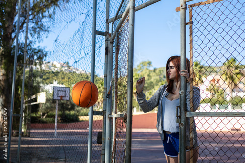 Young woman enjoys on the basketball court with her ball