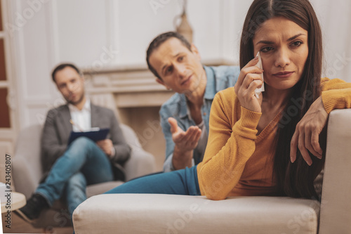 Dark-haired woman wearing yellow shirt crying during psychologist visit