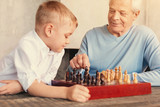 Little boy watching his grandfather making move in chess
