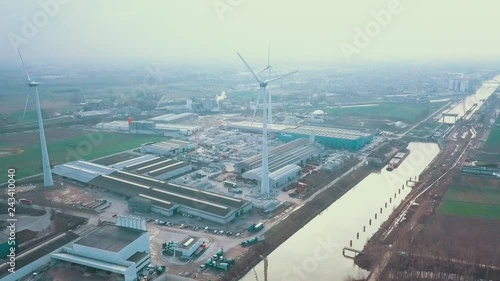 Fridge magnet Windmills standing in an industrial environment alongside a big canal