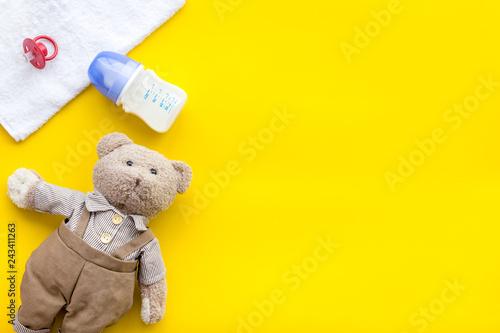 Leinwandbild Motiv Craft toys for kids. Handmade teddy bear, dummy and baby bottle with milk. Yellow background top view mock up