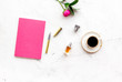 Feminine desk. Notebook and stationery near pink flowers and coffee on white background top view