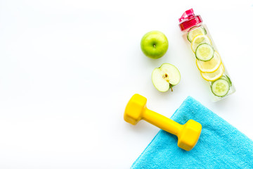 Healthy fruit water for sport, fitness. Bottle of water with lemon and cucumber near sport equipment dumbbells on white background top view copy space © 9dreamstudio