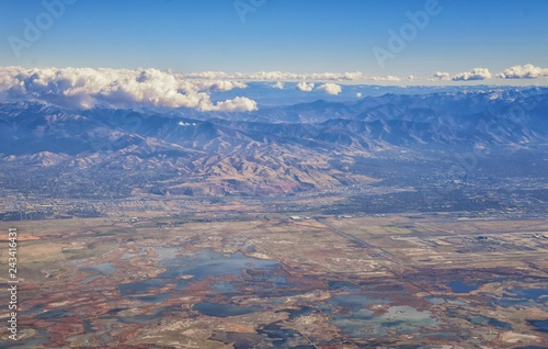 Aerial view of Wasatch Front Rocky Mountain landscapes on flight over Colorado and Utah during winter. Grand sweeping views near the Great Salt Lake, Utah Lake, Provo, Timpanogos, Lone and Twin Peaks  - 243416431