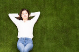 attractive asian woman lying on the lawn - 243421602