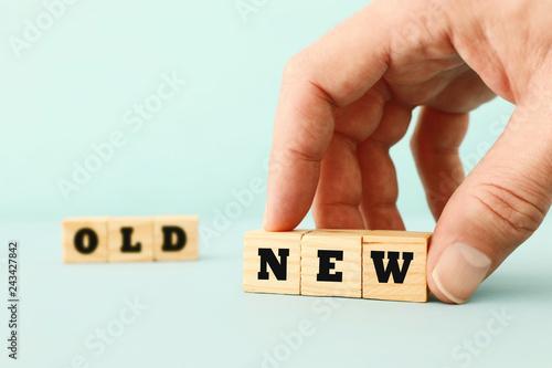 Leinwandbild Motiv man hand picking wooden cubes with the text NEW over wooden cubes with the text OLD.