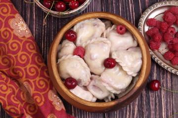 Homemade dumplings with cherries and raspberries