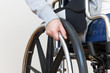 Detail of disabled woman holding a hand on wheel of a wheelchair.