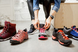 Woman trying different trail shoes for mountain hiking in the sports shop, close-up view with no face - 243439621