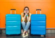 Young girl with long hair in glasses is sitting  on orange background between two suitcases. She wears yellow sweater with jeans. She looks upset.