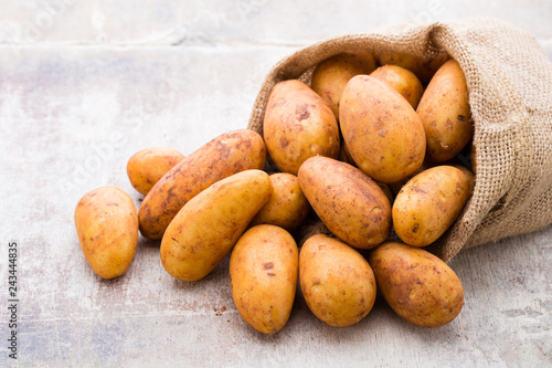 Poster A bio russet potato wooden vintage background.