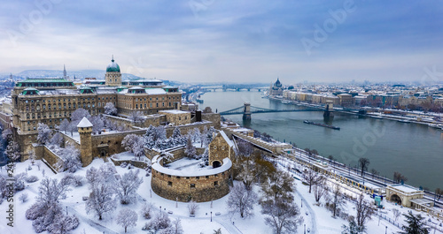 fototapeta na ścianę Budapest, Hungary - Aerial panoramic view of the snowy Buda Castle Royal Palace from above with the Szechenyi Chain Bridge and Parliament of Hungary at winter time