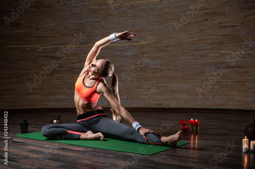 Woman on the yoga mat putting hand up while bending her back