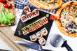 Food party table concept. Top view on snack pizza and sushi. Italian and Japanese cuisine on white wooden background with free copy space for text, logo or brand. Picture for restaurant - 243449473