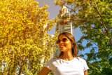 Portrait of a beautiful smiling young woman in a white shirt and sunglasses on a sunny day. - 243452273