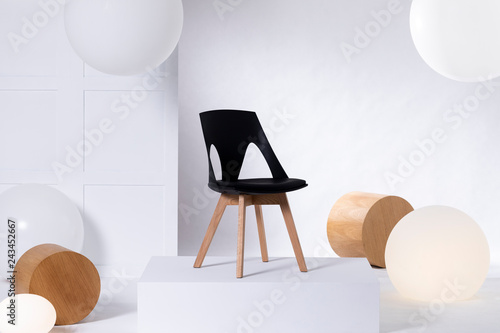 Stylish black chair on white platform in bright showroom interior with big balloons and wooden blocks