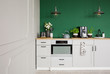 Empty green wall with copy space in elegant kitchen with white furniture,plants and coffee machine