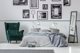 Armchair next to bed with grey pillows in bedroom interior with gallery and mirror. Real photo
