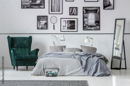 Armchair next to bed with grey pillows in bedroom interior with gallery and mirror. Real photo © Photographee.eu