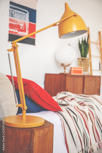 Close-up of a yellow lamp next to a bed in a bedroom interior
